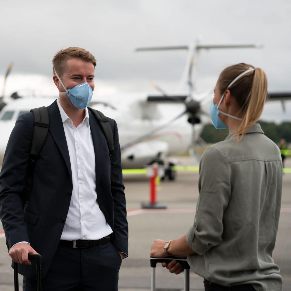 Mann und Frau mit Atemschutzmaske am Flughafen.