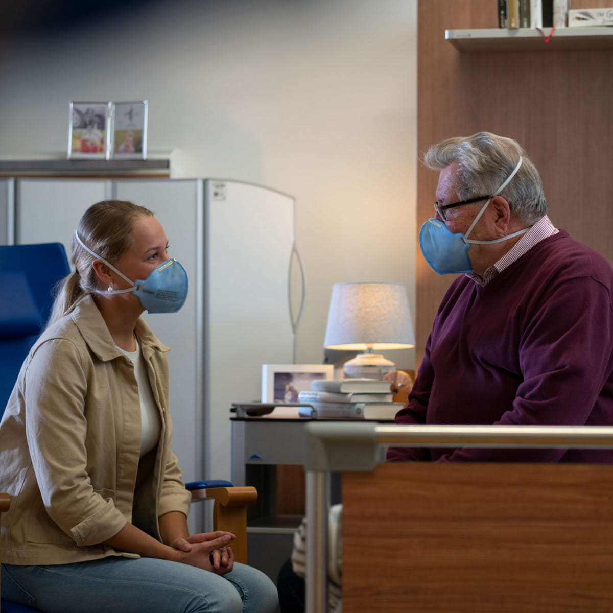 Mann und Frau im Seniorenheim mit Atemschutzmaske.